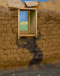 Man's shadow holding up a wooden window frame in an abandoned mud brick adobe