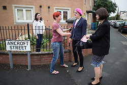 © Licensed to London News Pictures . 10/06/2016 . Manchester , UK . Comedian EDDIE IZZARD (2nd right) meets resident (and fan) RACHEL MORRIS (2nd left) when door knocking in Hulme , Manchester , in support of the Remain campaign , ahead of the UK's EU Referendum . Photo credit : Joel Goodman/LNP