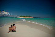 Lovers are sitting at bright sand beach of Nosy Iranja. Madagascar. Africa.