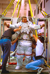 Stock photo of a man being suited up for the pool at the NASA Neutral Buoyancy Lab in Houston Texas