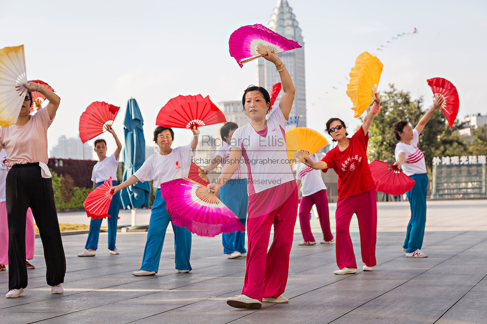 Chinese women perform early morning fan exercise on the Bund Shanghai, China