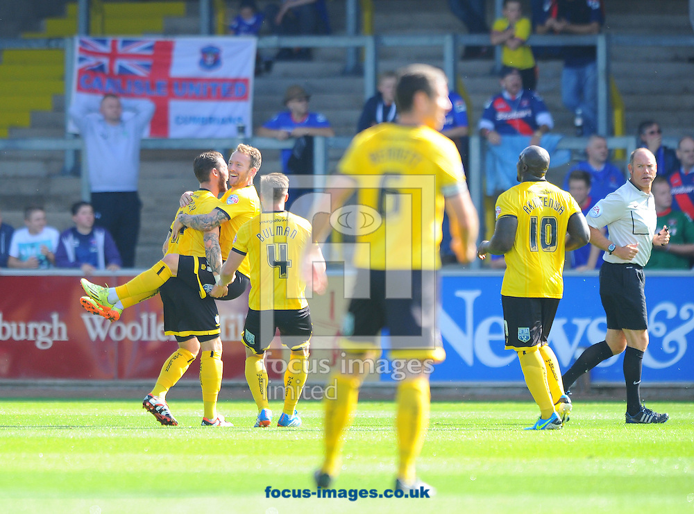 Sean Rigg of AFC Wimbledon (second left, top) celebrates scoring the opening goal of the match during the Sky Bet League 2 match at Brunton Park, Carlisle<br /> Picture by Greg Kwasnik/Focus Images Ltd +44 7902 021456<br /> 06/09/2014