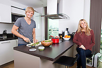 Portrait of happy man cutting vegetables while woman sitting at kitchen counter