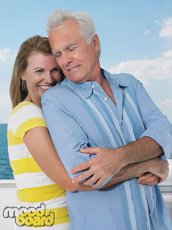 Middle-aged couple embracing on yacht