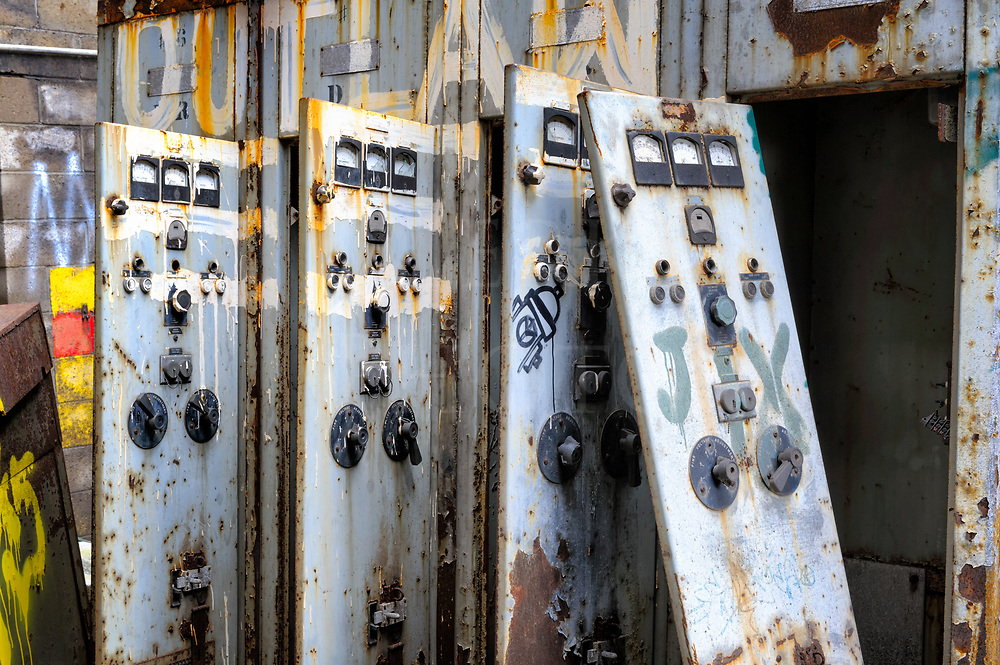 Electrical cabinet panels with graffiti hanging open and askew in a roofless control room at Carrie Furnace near Pittsburgh, PA.
