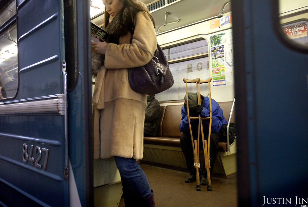 A disabled person crouches inside the Moscow metro on the ring line while a woman reads in the foreground. .The Moscow Metro, which spans almost the entire Russian capital, is the world's second most heavily used metro system after the Tokyo's twin subway. Opened in 1935, it is well known for the ornate design of many of its stations, which contain outstanding examples of socialist realist art.