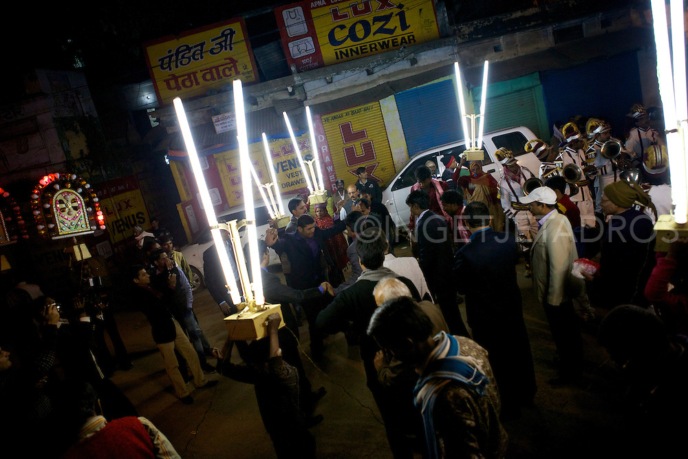 Male family members are dancing on the streets in Varanassi during a wedding party, surrounded by hired people who carry all sort of lightboxes on their heads