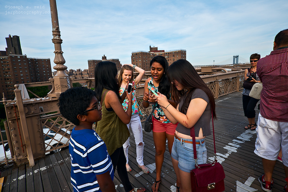 Young women with smartphones on Brooklyn Bridge, New York, NY, US