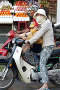 Cholon (Chinatown). Motorcycles during morning rushhour. Mother and child protected from polluted air and dust with a facial mask.