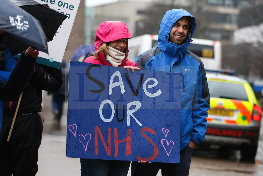 © Licensed to London News Pictures. 09/03/2016. Leeds, UK. Protesters and junior doctors demonstrate brave the rain and cold outside Leeds General Infirmary in West Yorkshire at the start of 48-hour walkout by junior doctors. This, the longest strike so far, comes after the government announced it would impose the new contracts upon junior doctors after negotiations broke down.  Photo credit : Ian Hinchliffe/LNP