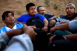 Men travel through downtown Nogales in the back of a pickup after the US Border Patrol caught them trying to illegaly enter the US and deported them.  They are on their way to a shelter to spend the night.