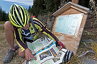 WA15246-00...WASHINGTON - Mount biker attempting to determination location from a Sno-Park sign and the Butler Washington Backcountry Discovery Route at the base of Skull and Crossbones Ridge.