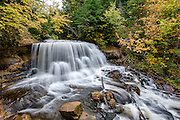 PICTURED ROCKS NATIONAL LAKESHORE - October 2016: Fall color starts to show around the upper section of Sable Falls during October in Pictured Rocks National Lakeshore near Grand Marais, Michigan in the Upper Peninsula. There are several named waterfalls in the park and a few un-named falls as well.<br />