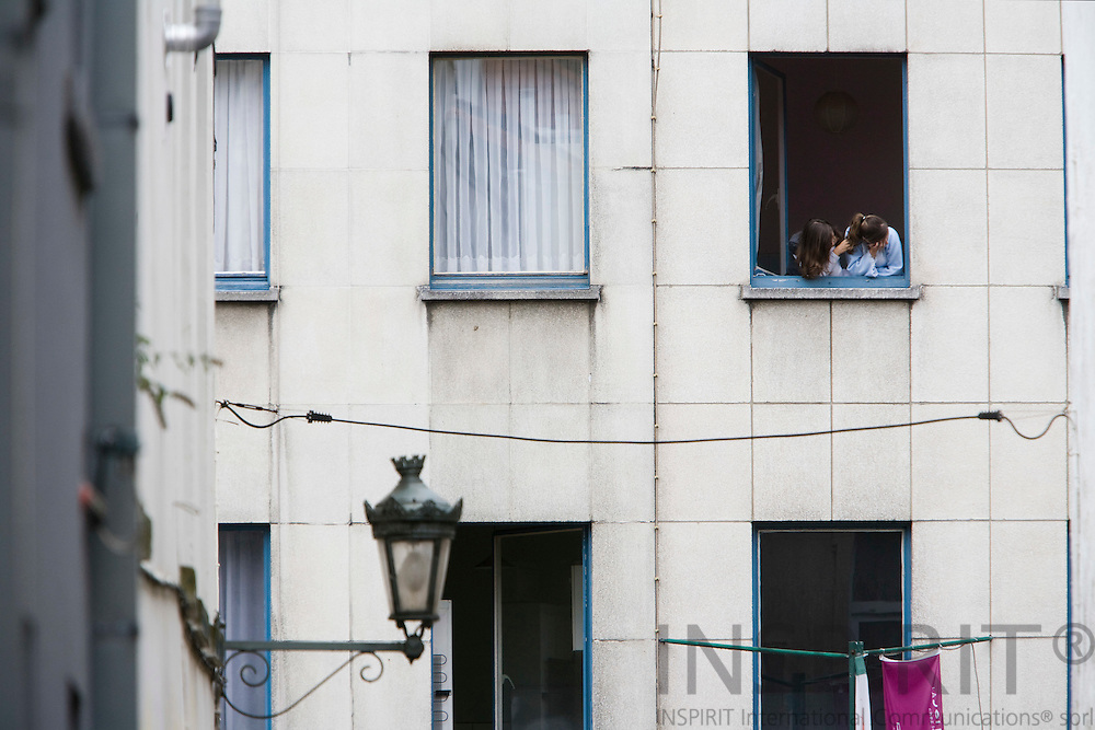 BRUSSELS - BELGIUM - 14 OCTOBER 2008 -- 2 girls in one apartment window looks out at the street from an apartment building at Marollen, an ancient district of Brussels. Photo: Erik Luntang