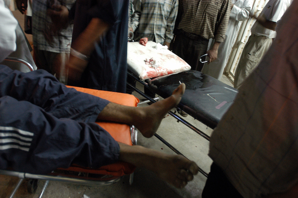 A man with multiple gunshot wounds and whose injuries are too severe to be treated at the al-Kadisia Hospital is wheeled onto the street to be transfered to another hospital. Thora City, formerly known as Saddam City, is a vast slum of 3 million Shiite Muslims, long marginalized and oppressed by Saddam Hussein's regime. The area is a hotbed of the violence and insecurity that has thrived with the absence of authority in the country..Baghdad, Iraq. 06 May 2003..Photo © J.B. Russell