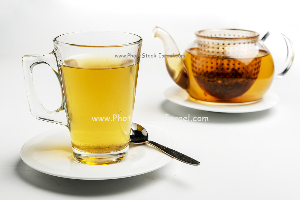 Glass of tea and teapot. The Tea bag can be seen in the pot