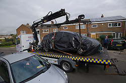 ©  London News Pictures. 15/10/2012. Harlow, UK. A burnt out vehicle being removed on the back of a low loader on Barn Mead, Harlow, Essex where three children and a woman have died and three others are in hospital following a house fire. Two boys aged 13 and six, a girl aged 11 and the woman were declared dead at the scene. A nine-year-old boy and a three-year-old girl have serious burns and a man has minor burns. Photo credit : Ben Cawthra/LNP