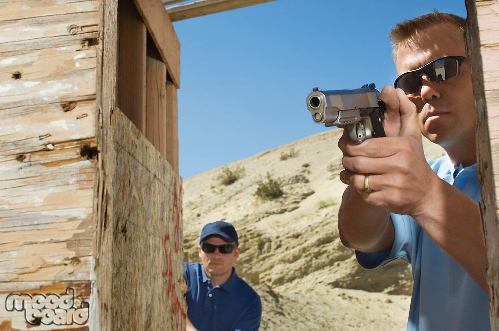 Man watching colleague aiming hand gun at firing range