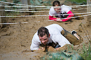 David Tompkins crawls through the mud at the old Army ROTC training course located at the Ridges during the O'Bleness Race for a Reason Mud Run, Saturday, April 27, 2013. The course included a four-mile run up to the old Army ROTC Course at the Ridges, through the Radar Hill Trail and back to Tail Great Park across from Peden Stadium. Race for a Reason, Race 4 A Reason, Annual Events, Events, Students, Faculty & Staff