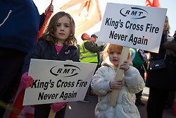 © licensed to London News Pictures. London, UK 18/11/2012. Daughters of a RMT Union member holding placards as RMT members gather outside King's Cross Station to commemorate the 25th anniversary of the fire at King's Cross Underground station, which killed 31 people, and to highlight safety fears. Photo credit: Tolga Akmen/LNP