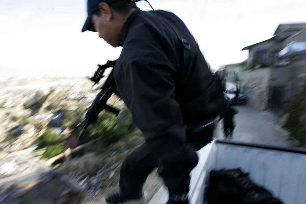 A Tijuana Police agents jumps out of a pick-up truck in route to search a home for illegal contraband during a drug sweep in Colonia Chula Vista in Tijuana, Mexico.