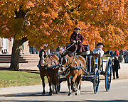 """An actor playing the wealthy Printer is carried in a two-horse carriage with driver, on Duke of Gloucester Street in Colonial Williamsburg. Colonial Williamsburg is the historic district of the independent city of Williamsburg, Virginia, which was colonial Virginia's capital from 1699 to 1780, and a center of education and culture. The capital straddled the boundary of two of the original shires of Virginia, James City Shire (now James City County), and Charles River Shire (now York County). Here, Thomas Jefferson, Patrick Henry, James Monroe, James Madison, George Wythe, Peyton Randolph, and dozens more helped mold democracy in the Commonwealth of Virginia and the United States. Motto: """"that the future may learn from the past.""""  The Historic Area exhibits colonial houses and American Revolutionary War history. Prominent buildings in Colonial Williamsburg include the Raleigh Tavern, the Capitol, The Governor's Palace, and Bruton Parish Church. Interpreters work, dress, and talk as they did in the era, teaching visitors. The 301-acre Historic Area is located immediately east of the College of William and Mary, which was founded at Middle Plantation in 1693. The new College, long a desire of the colonists, was a key factor in the establishment of the town as capital of Virginia in 1698 and its renaming for King William III of England shortly thereafter.  Jamestown and Yorktown, the other two points of the Historic Triangle, are linked to Colonial Williamsburg by the National Park Service's bucolic Colonial Parkway."""