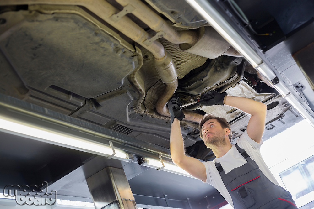 Low angle view of male automobile mechanic repairing car in repair shop