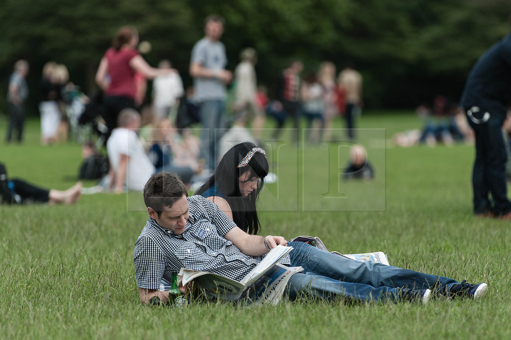 © Licensed to London News Pictures. 21/07/2012. London, UK.  A couple relax in the sun at the BT River of Music - Asia Stage at Battersea Park.  Photo credit : Richard Isaac/LNP