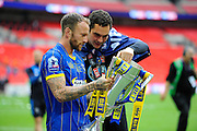 AFC Wimbledon midfielder Sean Rigg (11) and AFC Wimbledon goalkeeper James Shea (1) looking at the trophy during the promotion celebrations in the Sky Bet League 2 play off final match between AFC Wimbledon and Plymouth Argyle at Wembley Stadium, London, England on 30 May 2016. Photo by Graham Hunt.