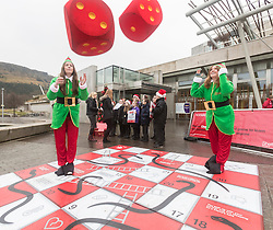 """Campaigners from Shelter Scotland raise awareness of their campaign """"Homelessness - Far From Fixed"""" outside the Scottish Parliament in Edinburgh. They are joined by carol singers from Corstorphine Primary School, a Christmas tree and a giant snakes and ladders board game - Chance Not Choice - which illustrates how life chances affect people's ability to keep a roof over their head.<br /> <br /> Pictured: Izzy Gaughan and Amanda Donaldson from Shelter Scotland"""