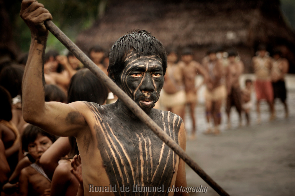 Viriunaveteri, Venezuela. Yanomami men with spears dancing a tribal dance in the central square..The village of Viriunaveteri consists of 15 huts around a muddy square. It's situated in the Venezuelan Amazone several days by boat from the nearest town. This community on the banks of the Casiquiare is one of the few Yanomami villages that actually has some contact with the outside world. Most other tribes live deeper in the jungle.