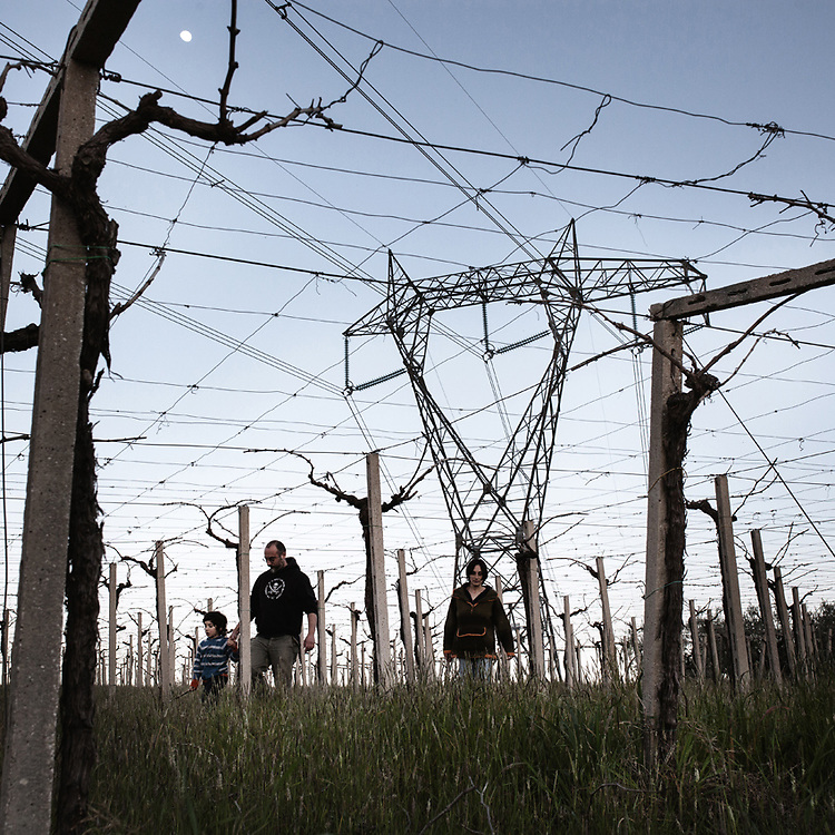 Silvia Ferrante walks with her family in the vineyard overshadowed by a high voltage pylon. Along with her husband she had decided to leave the chaos of Rome to raise their child, Libero, in the unspoiled nature. Right after moving in, a few months after the birth of their son, they found out that a 70 meters high transmission tower would be built within 50 meters from their house.