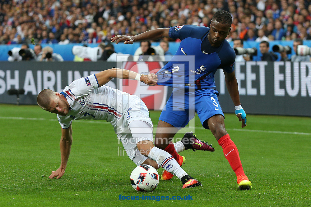 Johann Gudmundsson of Iceland and Patrice Evra of France in action during the quarter final match at Stade de France, Paris<br /> Picture by Paul Chesterton/Focus Images Ltd +44 7904 640267<br /> 03/07/2016