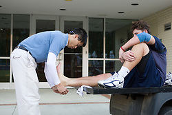 05 November 2007: North Carolina Tar Heels men's lacrosse athletic trainer Chun-Man Fong treats freshman Kevin Piegare in a practice on Navy Field in Chapel Hill, NC.