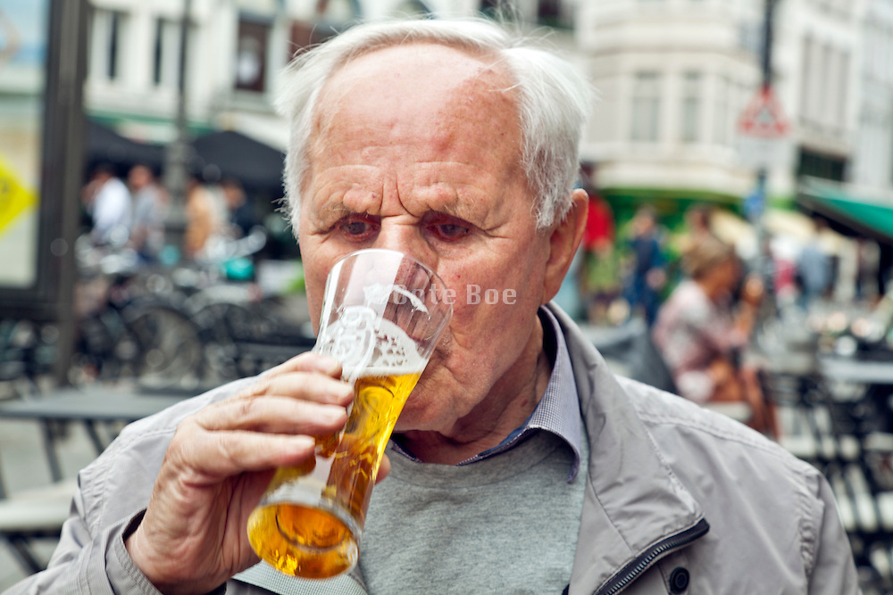 senior man drinking a beer on a terrace