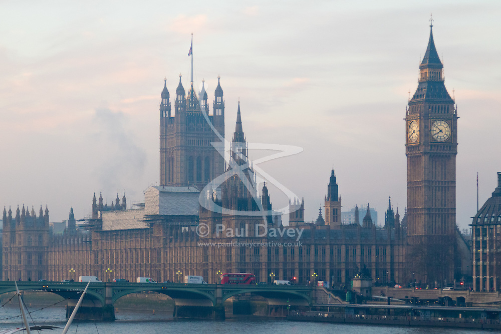 London, January 24th 2017. Photographed from Hungerford Bridge, the early morning light illuminates clouds and buildings of the city's skyline, with the predicted fog failing to appear. High pressure over the UK has caused pollution alerts as fumes are trapped beneath a cold layer of air.PICTURED: The early morning sky creates a soft, pastel-toned backdrop for the Houses of Parliament.
