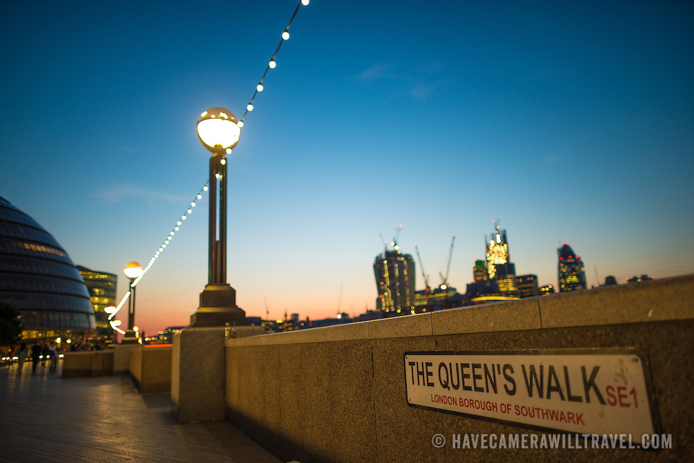 The Queens Walk in the London Borough of Southwark, near the Tower Bridge, at dusk, with the city lights of downtown London in the background.