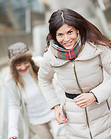 Smiling young woman climbing stairs with friend outdoors