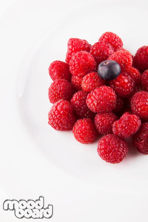 Blueberry over raspberries against white background