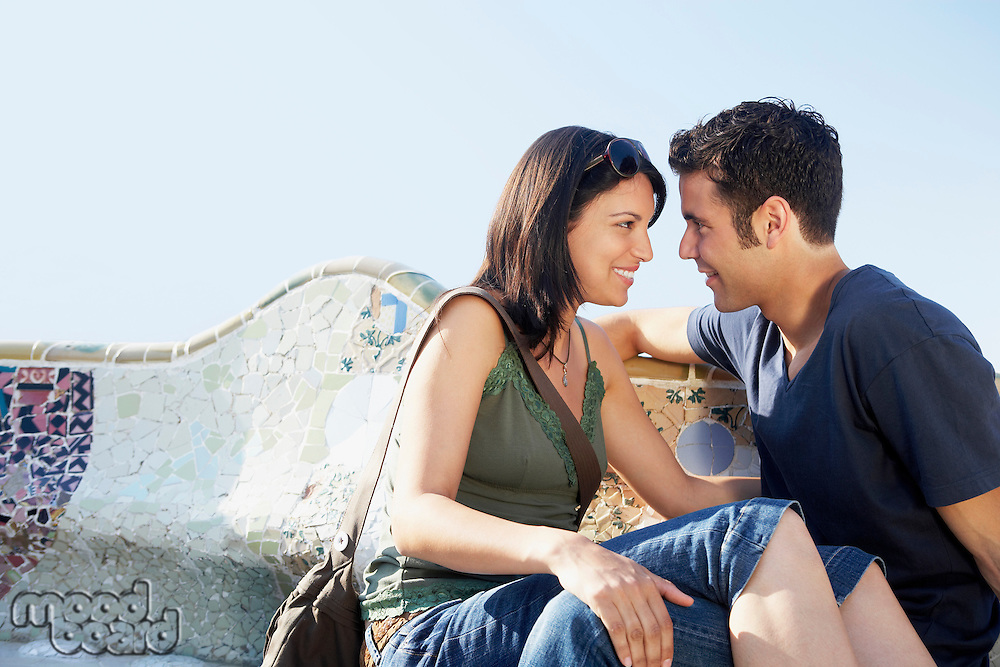 Young couple sitting on stone bench portrait