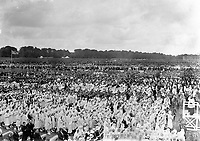 Mr. Vincent O'Brien (on right) conducting the white robed childrens choir which led the congrgational singing in the Phoenix Park for the Eucharistic Congress in 1932.<br /> (Part of the Independent Newspapers Ireland/NLI collection.)