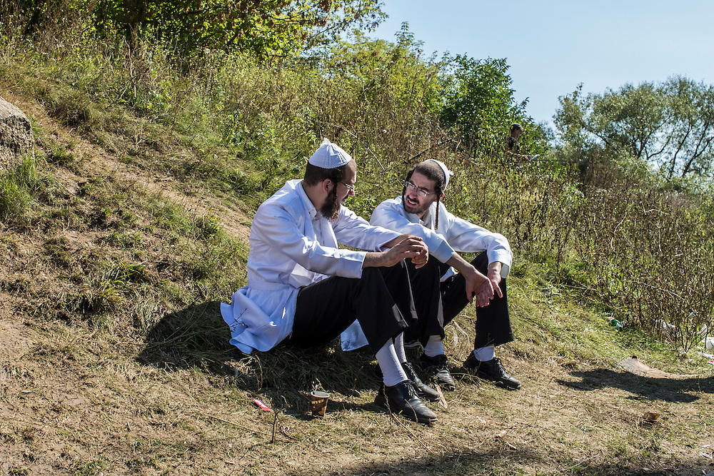 UMAN, UKRAINE - SEPTEMBER 14: Hasidic pilgrims sit along a riverbank near the burial site of Rebbe Nachman of Breslov on September 14, 2015 in Uman, Ukraine. Every year, tens of thousands of Hasidim gather for Rosh Hashanah in the city to pray at the holy site. (Photo by Brendan Hoffman/Getty Images) *** Local Caption ***