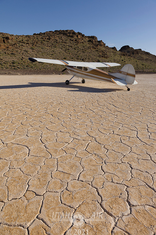 Cessna 170 parked on the dry lake bed in the Thule Valley Hardpan (Ibex)