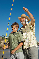 Boy and grandfather showing off fish on beach