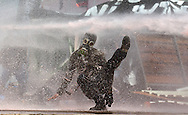 A protestor hit by pressured water sprayed from riot police water cannon during clashes Taksim Square Istanbul, Turkey on 11 June 2013.  Demonstrations against the Islamic-conservative government of Prime Minister Recep Tayyip Erdogan began on 31 May when a police crackdown against a peaceful sit-in staged by environmentalists angered over a development project in Istanbul escalated into larger battles between law enforcement and demonstrators.