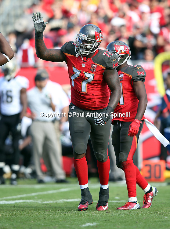 Tampa Bay Buccaneers defensive tackle Tony McDaniel (77) gets a high five as he celebrates after stuffing New Orleans Saints running back Tim Hightower (34) on a third quarter pass in the flat during the 2015 week 14 regular season NFL football game against the New Orleans Saints on Sunday, Dec. 13, 2015 in Tampa, Fla. The Saints won the game 24-17. (©Paul Anthony Spinelli)