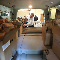 Kay Collins, center left, and Mark Burelson begin filling a truck with boxes of sack lunches from United Way and First United Methodist Church for students in Tupelo Publice School District twice a month.