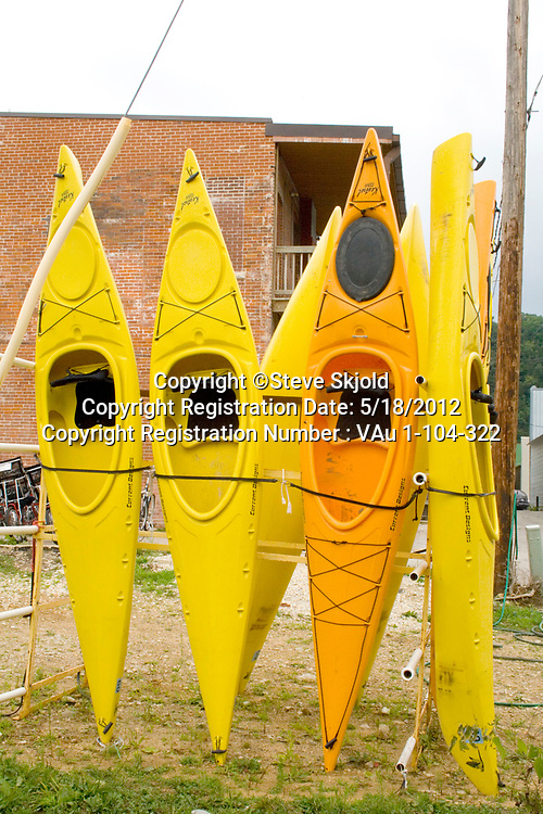 Rack of yellow kayak rentals near the Root River. Lanesboro Minnesota MN USA