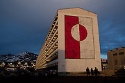 "Greenland flag mural on apartment block P, Nuuk, Greenland. Block P is the largest apartment blog in downtown Nuuk, the capital of Greenland.  More than 1% of Greenland's 57,000 population reportedly live in this building. On the end is the Greenland flag. This image was made just two days before the June 21st 2009 self-governance ceremony, in which Denmark handed over more power to the local population. Block P was built by the Danish government in the 1960s to modernize and urbanize the Greenlandic infrastructure by moving people away from coastal settlements which were though to be ""unprofitable, unhealthy and unmodern"". The same could be said for these 'new' buildings. Block P was demolished in October 2012. Copyright 2009 Dave Walsh"