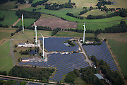 A field of solar panels share tie in to grid with wind turbines.